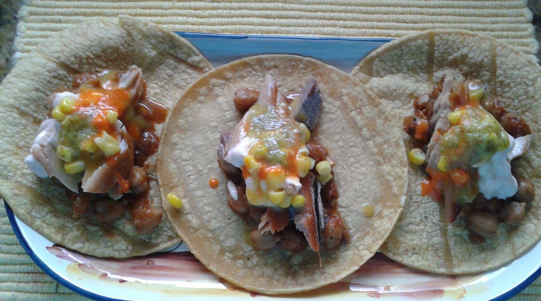 Corn tortillas with smoked salmon, chipotle chickpeas, salsa and Sriracha crema