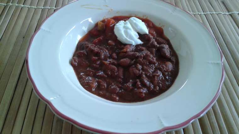 Pinto beans cooked with organic diced tomatoes, taco seasoning, ground cumin and cocoa powder topped with salsa and sour cream