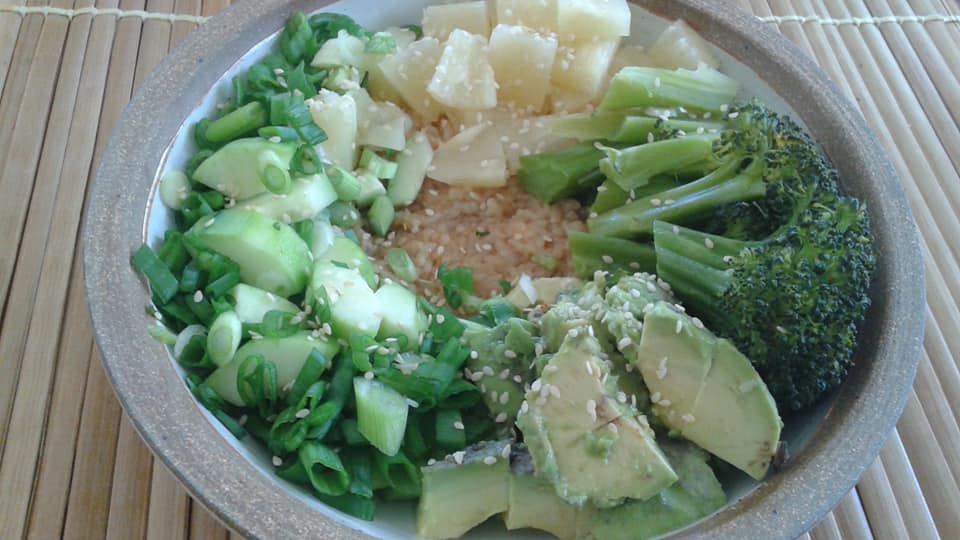 poke bowl: seasoned rice, steamed broccoli, green onion, cucumber, avocado and pineapple with a sprinkle of sesame seeds