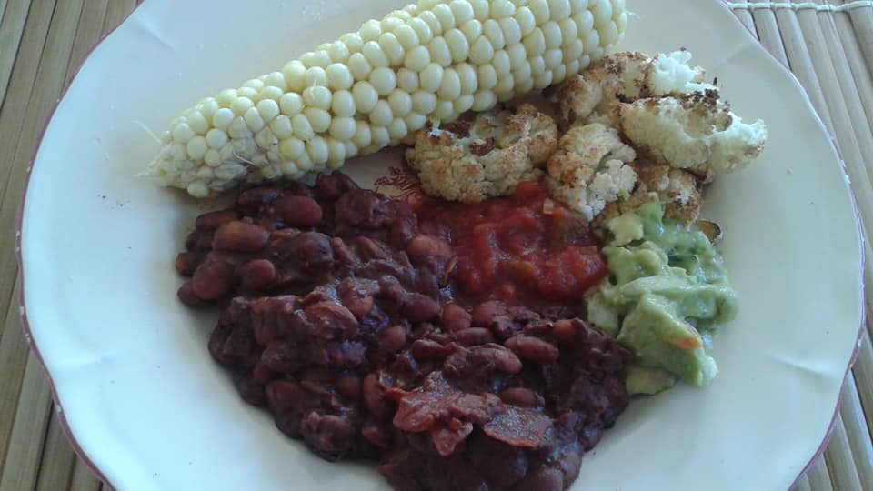 Cocoa pinto beans, roasted cauliflower and corn on the cob with a side of salsa and guacamole